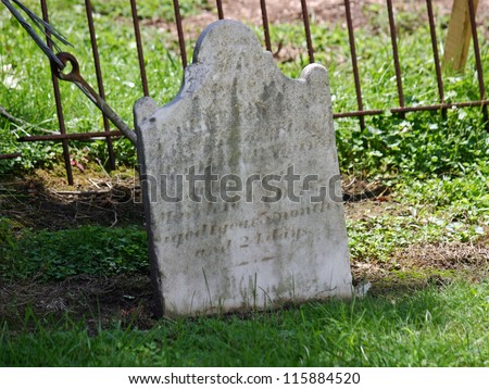 An old tombstone outside of a church in NJ - stock photo