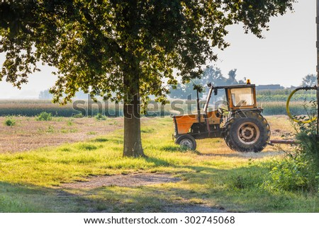 an old tractor is resting after a tiring day in the shade of a tree in the Italian countryside while the summer sun is setting - stock photo