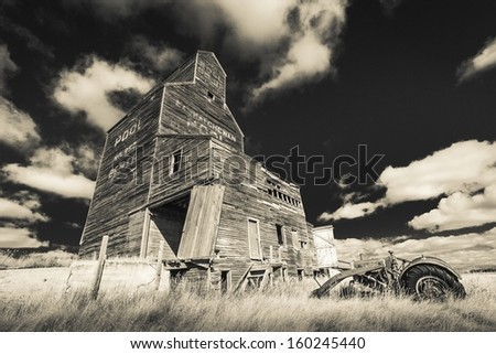 An old tractor rusts away near a grain elevator in the ghost town of Bents, Saskatchewan.  Processed with an infrared filter. - stock photo