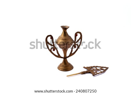 An old traditional mascara container make from copper with the stick put down aside isolated on white background  - stock photo
