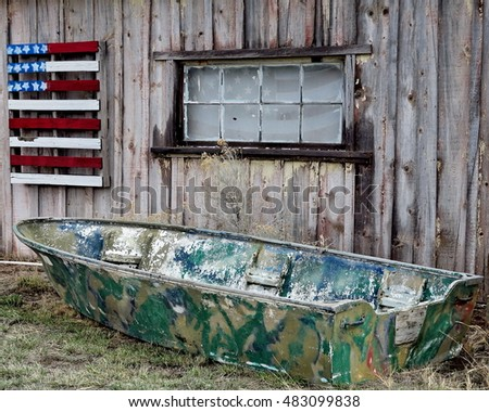 An old truck top camo boat sits in front of an old building with a wooden American flag out in Oregon's Outback.