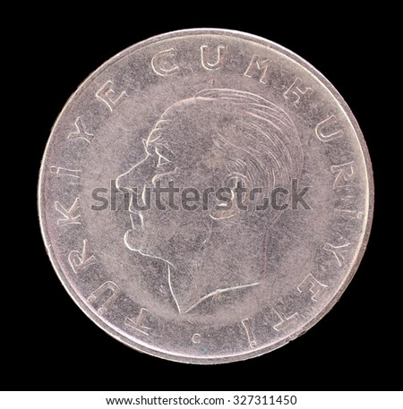 An old Turkish lira coin depicting the portrait of the first President of Turkey, Mustafa Kemal Ataturk. Image isolated on black background