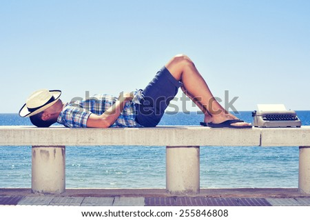 an old typewriter with a blank page and a young man lying down in a street bench near the sea, while is waiting for inspiration - stock photo