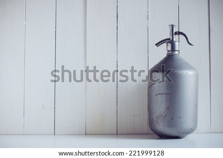 An old vintage aluminum siphon, antique seltzer soda bottle, painted white wooden board, rustic background - stock photo