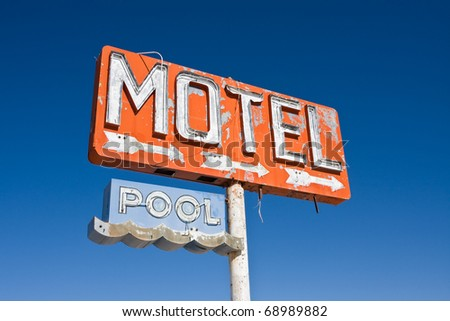 An old vintage, neon sign points to a motel that was never built. - stock photo