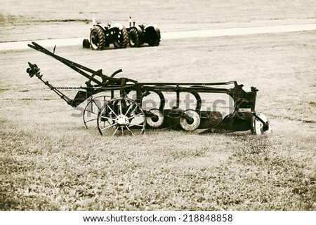 An old vintage plow sits outside on a farm field.  Filtered to give retro, vintage look.