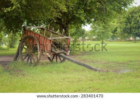 An old wagon sits in a field.