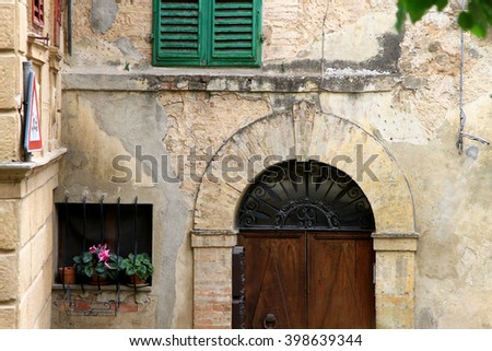 An old wall and arched doorway in Montalcino,Tuscany, Italy - stock photo