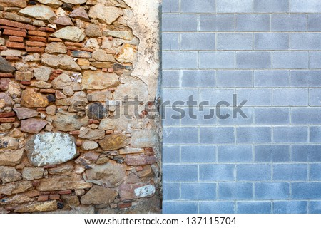 An old wall meets a new one - the clash of styles conveys an interesting visual and conceptual contrast: old vs new, chaos vs order, organic vs geometric, variety vs uniformity. - stock photo