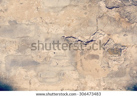 An old wall with cracks in the concrete. Also some red brick wall is appearing from the cracks. This image is usable nicely as background. Image has a vintage effect applied.