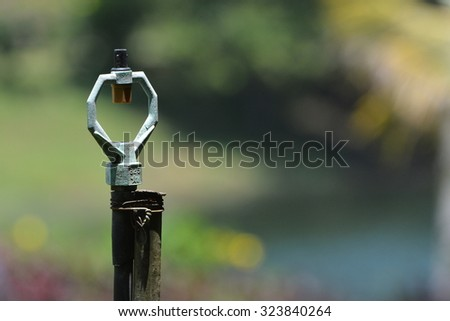 An old water sprinkler with blurred background