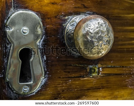 An old, weathered brass door knob and key hole with layers of old polish. - stock photo