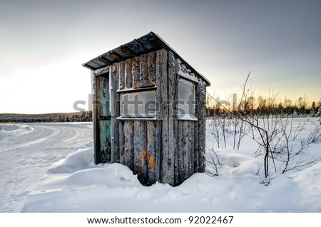 an old weathered shack in a winter landscape - stock photo