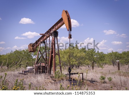 An old west Texas pump jack works away in a remote pasture