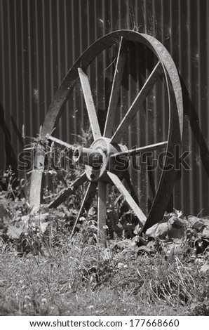 An old wheel cart in deserted the farm. (BW) - stock photo