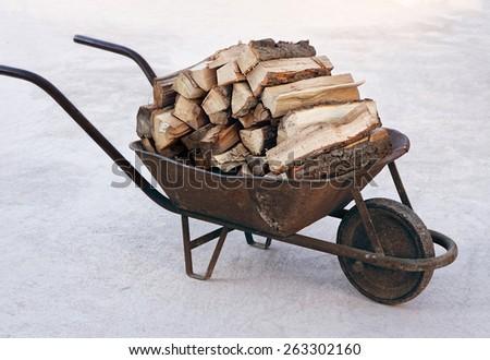 An old wheelbarrow full of firewood - stock photo