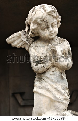 An Old White Crumbling Cherub Angel Statue - stock photo
