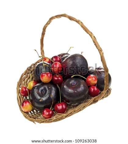An old wicker basket filled with ripe red cherries and plums on a white background. - stock photo