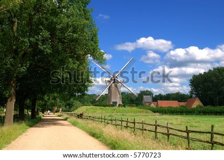 An old windmill against a blue vibrant sky along the road in Belgium. Vintage, preservation, tourism concept.