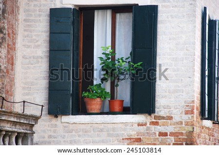 An old window on a brick wall in Venice