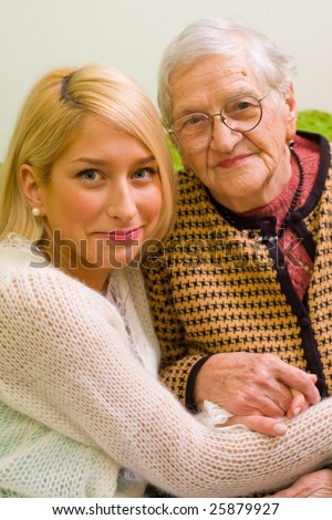 An old woman and her grandchild sitting close to each other (focus on the young woman) - part of a series.