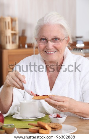 An old woman eating breakfast. - stock photo