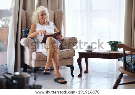 An old woman enjoying her book in her lounge - stock photo
