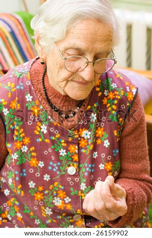 An old woman holding a pill in her hand - part of a series.