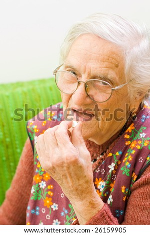 An old woman holding a pill in her hand, preparing to eat that - part of a series.