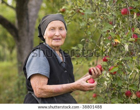 An old woman in her garden, holding in hand red apples.