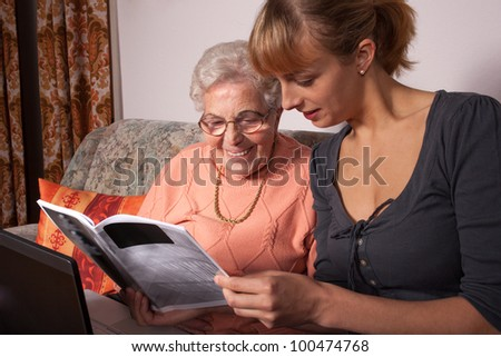 An old woman is a laptop explained by her granddaughter - stock photo