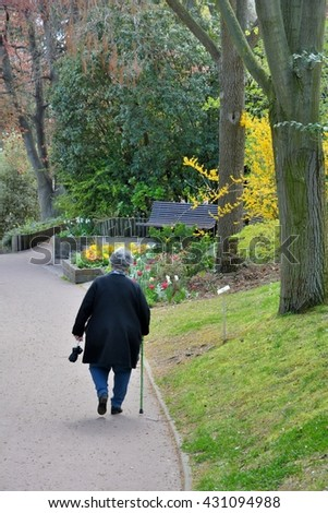 An old woman is walking in a square