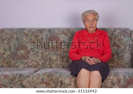 An old woman sits on the couch