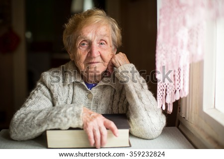 An old woman sits with a book. - stock photo