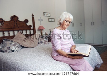 An old woman sitting on her bed reading a book with copyspace - stock photo