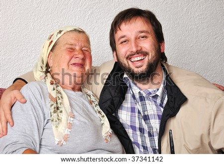 An old woman with good funny face and young man beside - stock photo