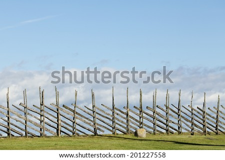 An old wood fence with a green country field behind it. Estonia, Saaremaa - stock photo
