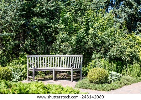 An old wooden bench on a brick walkway in a green park - stock photo