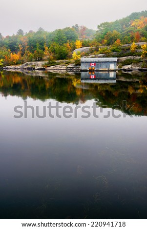 An old wooden boat house with a Canada flag on its wall is on a calm lake surrounded by a rocky landscape and colorful trees on a misty autumn morning.  - stock photo