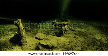 An old wooden boat lies shipwrecked on the bottom of a lake. - stock photo