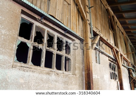 An old wooden building with broken windows