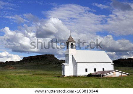 An old wooden church against a hill and grassland. Sunlight on the church, lifting it off the background. Shot in a remote rural area in Midwestern USA. - stock photo