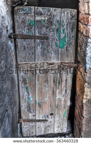 an old wooden door in an old brick wall - stock photo
