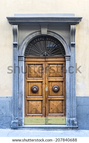 An old wooden double door with ornate handles surrounded by a carved stone decorative frame in a cement rendered wall. - stock photo