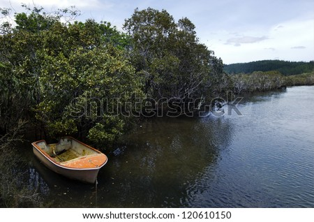 An old wooden fishing boat in a river.