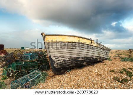 An old wooden fishing boat rests on a shingle beach alongside abandoned lobster pots - stock photo