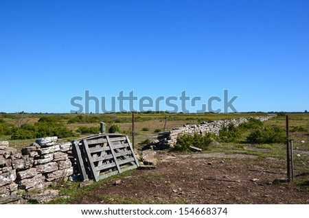 An old wooden gate at a stonewall on the great alvar plain on the island Oland in Sweden - stock photo