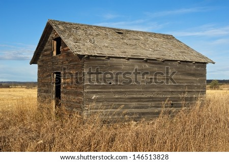 An old wooden granary in fall with dry weeds and grass in the foreground and a harvested field in the background - stock photo
