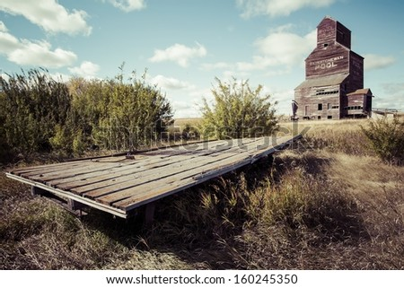 An old wooden hay trailer by an old grain elevator. - stock photo