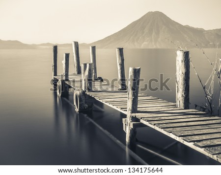 An old wooden pier juts out into lake Atitlan in Guatemala with volcano in background - long exposure - stock photo